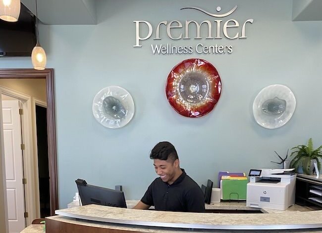 Receptionist at desk welcoming new patients